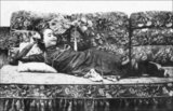 Studio photograph of a Vietnamese prostitute reclining on a bed with a fan, Saigon, c.1910